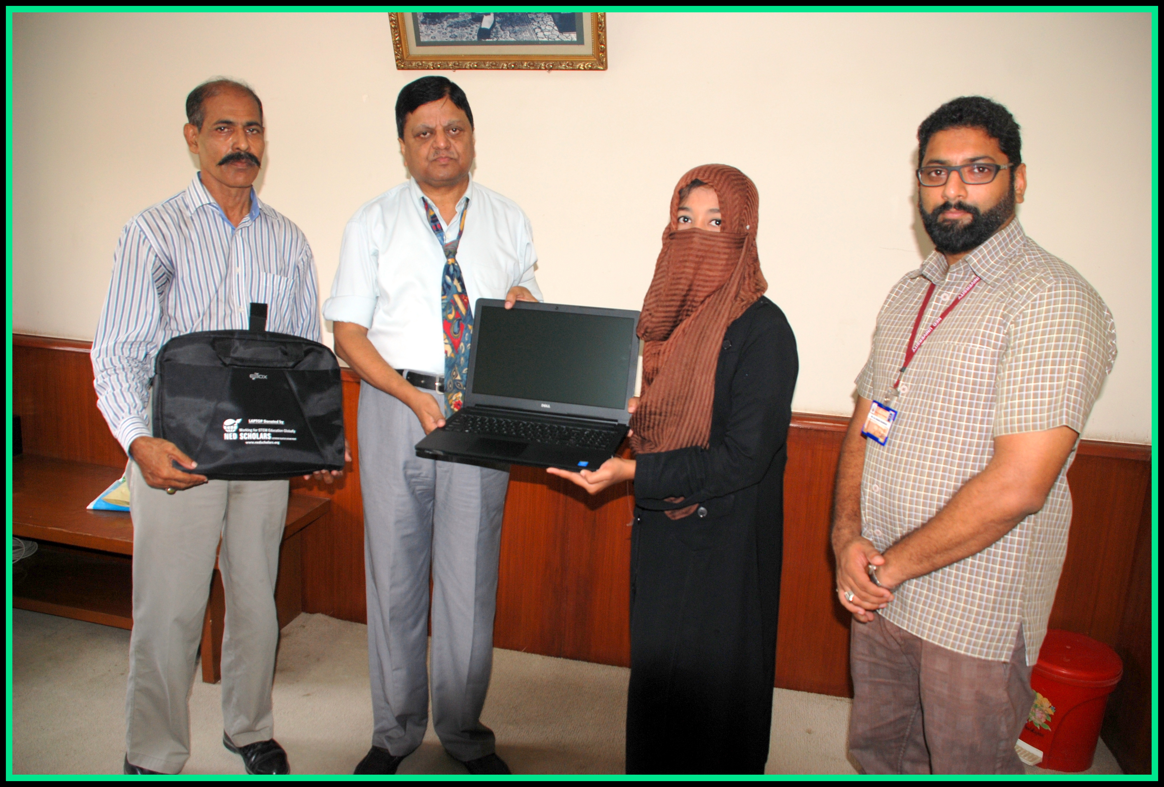 Amna receiving her laptop from NED VC